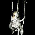 Fabric figure of child on a swing