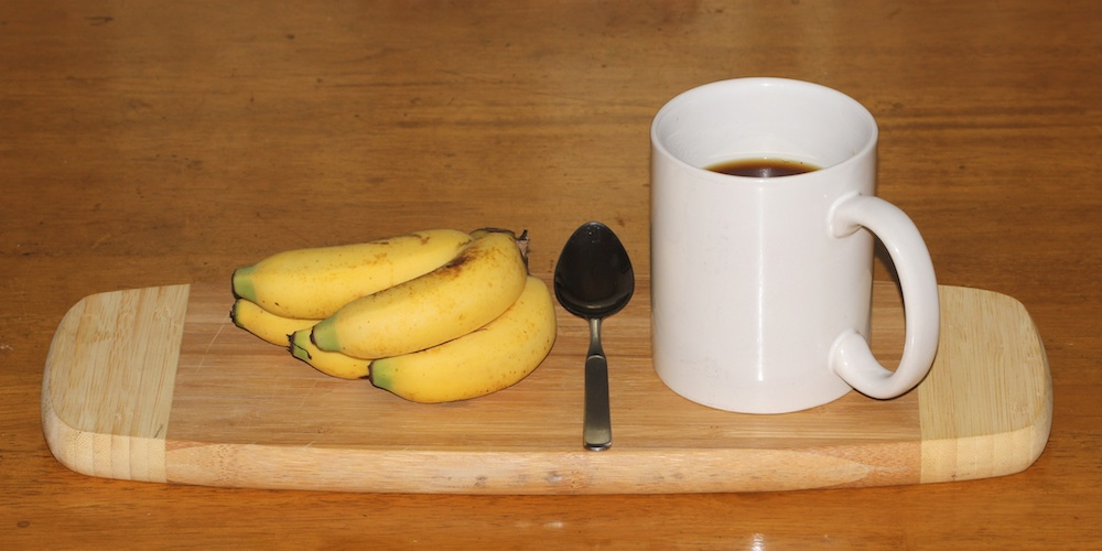 small bananas with a teaspoon and coffee mug