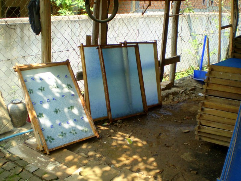 Screens of new paper drying against a fence
