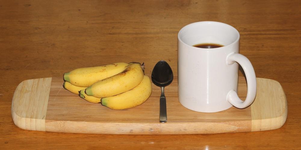 small bananas with a teaspoon and coffee mug