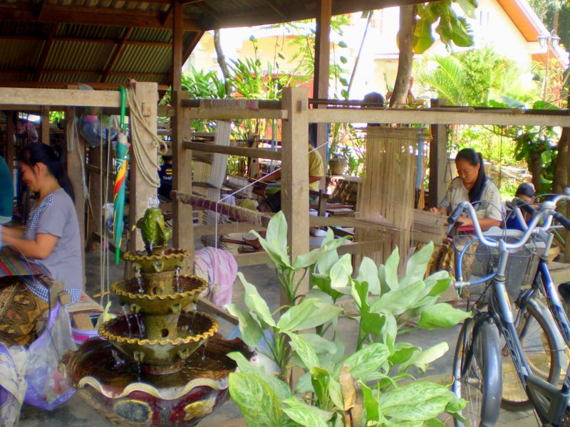 Silk weavers working on hand looms